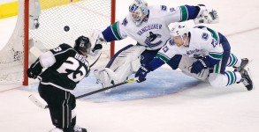 >Los Angeles Kings captain Dustin Brown scores in the third period, his fourth goal of the playoffs, on Vancouver Canucks goalie Cory Schneider as defenceman Alexander Edler dives across too late.